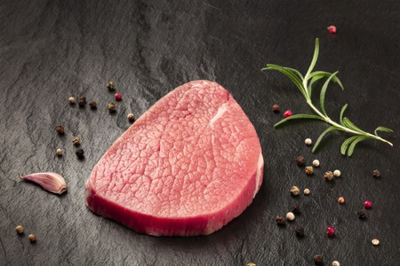 A photo of a steak of eye round beef, a raw cut, with rosemary, pepper and garlic on a black background with copy space