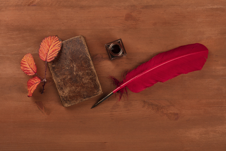 Autumn Poetry. A photo of an old book with a thorny branch with vibrant leaves, an ink well, and a quill, shot from above on a dark wooden background with copy space