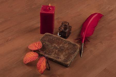 Poesía de otoño. Una foto de un libro antiguo con una rama espinosa con hojas vibrantes, un tintero, una pluma y una vela encendida sobre un fondo de madera oscura con espacio de copia