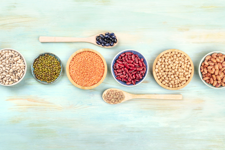 Various types of pulses, shot from above on a teal background with copy space. Red kidney, pinto, and black beans, lentils, chickpeas, soybeans, black-eyed peas Stock fotó