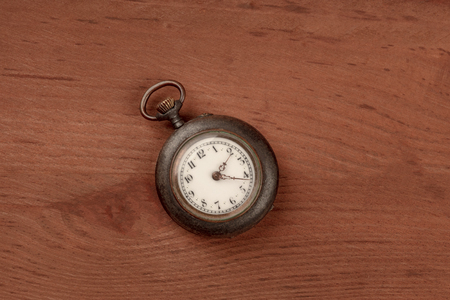 A vintage pocket watch, shot from the top on a dark rustic wooden background with a place for text