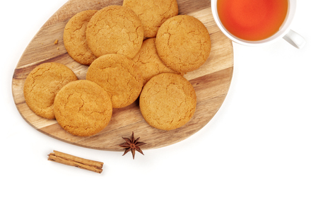 A closeup of gingersnaps with a cup of tea, a cinnamon stick, and an anise star, shot from above on a white background with copy space