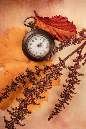 A vintage pocket watch with autumn leaves, shot from the top on an old paper background Standard-Bild - 112766919