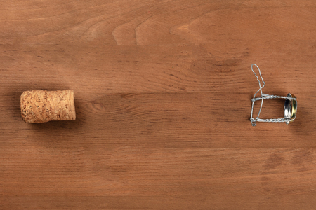 A photo of a champagne cork and closure, shot from the top on a rustic wooden background with a place for text Stock Photo