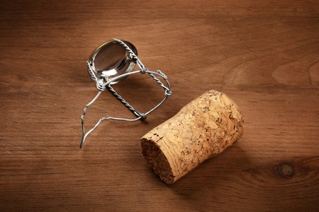 A closeup photo of a champagne cork and a closure on a dark rustic wooden background with a place for text Imagens