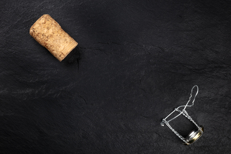 A photo of a champagne cork and closure, shot from the top on a black background with copy space Stock Photo