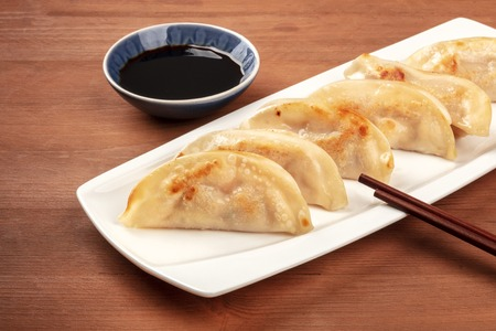 A closeup photo of gyozas, Asian dumplings, with soy sauce and chopsticks, on a rustic wooden background