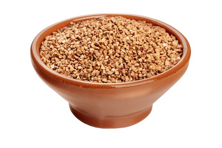 A photo of raw buckwheat in an earthenware bowl, isolated on a white background with a clipping path