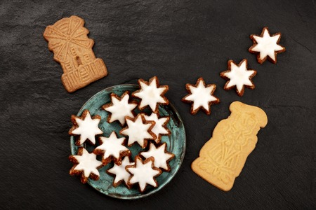A photo of an assortment of traditional Christmas Spekulatius and Zimsterne cookes, shot from above on a dark background with copy space Stock Photo