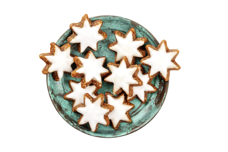 A closeup photo of Zimsterne, traditional German cinnamon star cookies, shot from the top on a white background, isolated with a clipping path