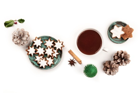 Zimsterne, traditional Christmas cinnamon star cookies, shot from the top on a white background with hot chocolate, spices, a toy Christmas tree, pine cones, and a place for text 写真素材