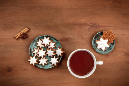 Christmas Zimsterne, cinnamon star cookies, shot from the top on a rustic wooden background with hot chocolate and a place for text