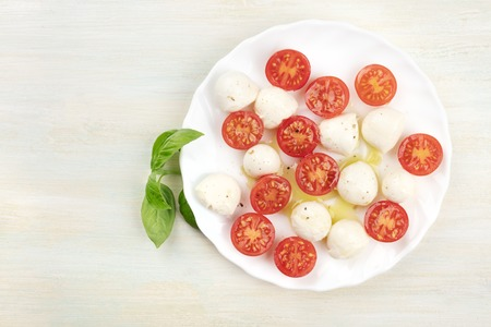 A plate of Italian Caprese salad with Mozzarella cheese, cherry tomatoes and basil leaves, shot from above on a light background with copy space