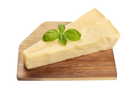 A piece of aged Parmesan cheese with fresh basil leaves, isolated with a cutting board on a white background with a clipping path