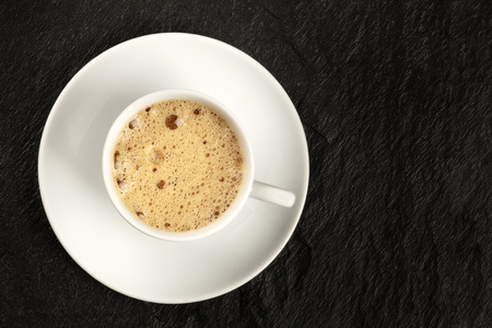 A cup of regular coffee with foam on a dark black background with a place for text