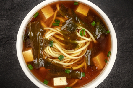 A closeup photo of a bowl of miso shiru soup with tofu, scallions, noodles, and wakame seaweed, shot from the top on a black background Stock fotó