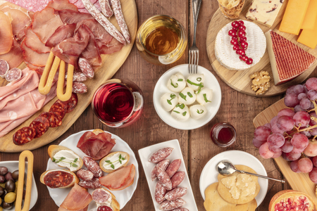 Charcuterie Tasting. Many different sausages and hams, deli meats, and a selection of cheeses, shot from above on a rustic background with glasses of wine, olives and grapes