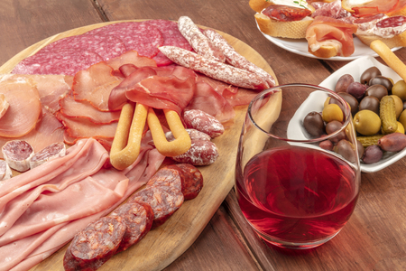 Charcuterie Tasting. A photo of many different sausages and hams, cold cuts, on a dark rustic background with a glass of red wine