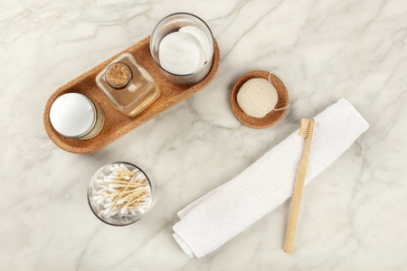 An overhead photo of sustainable toiletries. Homemade lotions, cotton pads, bamboo toothbrush, natural Konjac sponge, and biodegradable bamboo cotton swabs