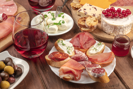 Wine tasting and pairing. Wineglasses with cheese sandwiches and a cheese platter on a dark wooden background Stock Photo