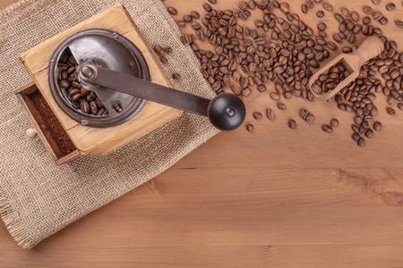 An overhead photo of a vintage coffee grinder with roasted coffee beans, shot from the top on a rustic background with copy space
