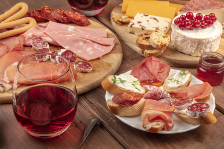 Wine tasting and pairing. A wineglass with charcuterie, sandwiches and a cheese platter on a dark wooden background