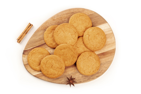Ginger biscuits, a cinnamon stick, and an anise star, shot from the top on a white background with a place for text