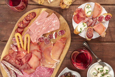 Gourmet Charcuterie. Many different sausages and hams, cold cuts, shot from the top on a dark rustic background with wine and sandwiches