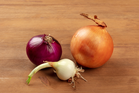 An assortment of various types of onions of a dark rustic wooden background with copy space