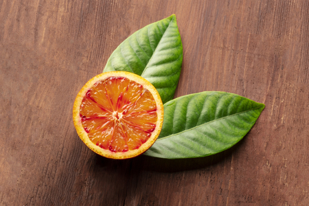 A closeup of a fresh organic blood orange, shot from above on a dark rustic wooden background with green leaves and copy space