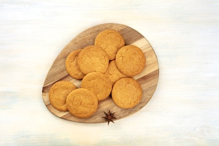 Gingersnaps on a wooden tray, shot from above with an anise star and copy space