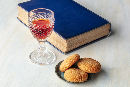 A photo of a glass of sweet wine with cookies, a book, and a place for text