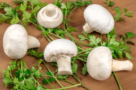 A photo of champignon mushrooms on a rustic wooden background with fresh parsley leaves