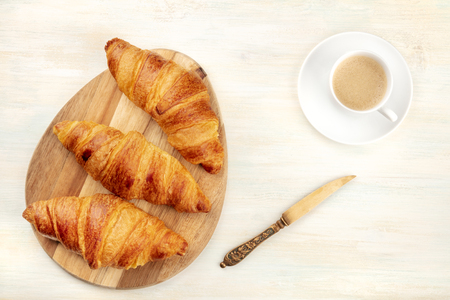 A high key photo of croissants with coffee and a knife, shot from the top on a white wooden background with copy space