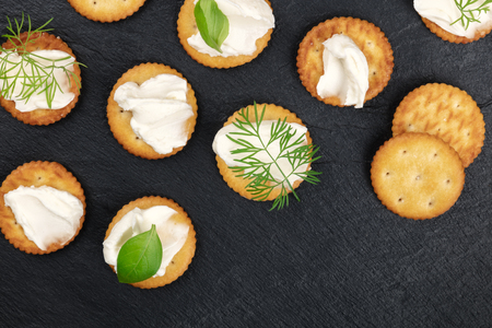 A photo of salt crackers with soft cream cheese spread and herbs, shot from the top on a black background with a place for text Archivio Fotografico - 119721395