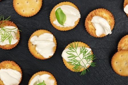 A closeup photo of salt crackers with soft cream cheese spread and herbs, shot from above on a black background Archivio Fotografico - 119793456
