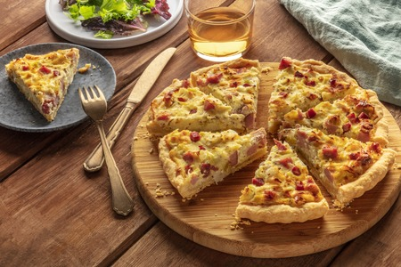 A photo of a quiche with a piece cut off, with wine and salad leaves on a dark rustic wooden background with a place for text Reklamní fotografie