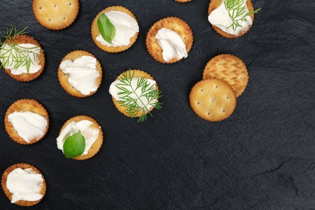 Salty crackers with soft cream cheese spread and herbs, shot from above on a black background with copy space Archivio Fotografico - 120138845