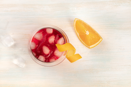 A vibrant cocktail with orange curl garnish, with ice cubes and an orange slice, shot from the top on a white wooden background with a place for text