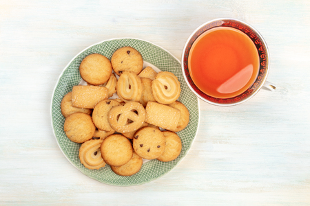 Danish butter cookies on a plate, shot from above with a vintage cup of tea on a white wooden background with a place for text