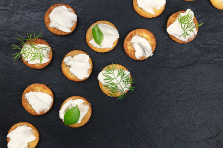 Many salt crackers with a cream cheese spread and fresh herbs, shot from the top on a black background with copy space Archivio Fotografico - 120309154