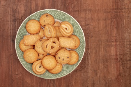 Danish butter cookies, shot from above on a dark rustic wooden background with copy space