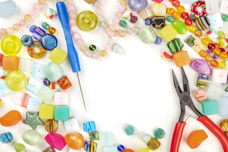 An overhead photo of many different beads with tools for making jewellery, on a white background with copy space 写真素材