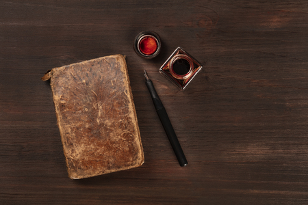 An old journal with a nib pen and an ink well, shot from the top on a dark wooden background with a place for text
