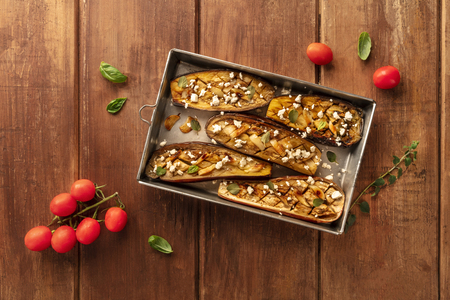 Vegan Italian food. Baked eggplants with organic cherry tomatoes, herbs, and lactose-free cheese, shot from the top on a wooden background with a place for text