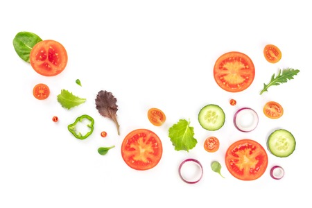 Fresh vegan vegetable salad ingredients, shot from above on a white background. A flat lay composition with organic tomato, cucumber, peppers, onion slices and mezclun leaves