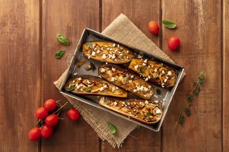 Vegan Italian food. Baked eggplants with organic cherry tomatoes, herbs, and lactose-free cheese, shot from above on a wooden background with copy space