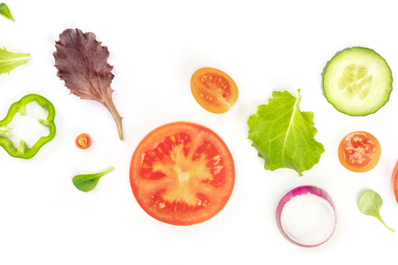 A closeup photo of fresh vegan vegetable salad ingredients, shot from the top on a white background. A flat lay composition with organic tomato, cucumber, peppers, onion slices and mezclun leaves