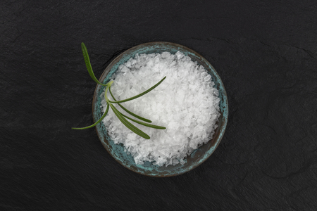 A bowl of rosemary infused sea salt, shot from the top on a black background with copy space