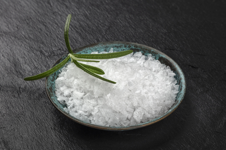 A closeup of a bowl of rosemary infused sea salt on a black background